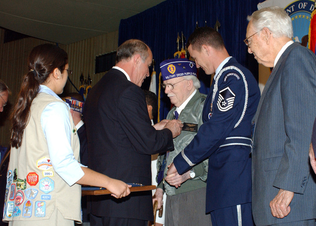Councilman Carrol Schubert (second from left), Chairman of the Board of the San Antonio City Council, Texas, pins a World War II 60th Anniversay pin on retired MASTER SGT. John Lawlor (center) during San Antonio's Honoring of WWII Veterans Ceremony on April 3, 2005, at Lackland Air Force Base, Texas. (PHOTO by Alan Boedeker) (Released)