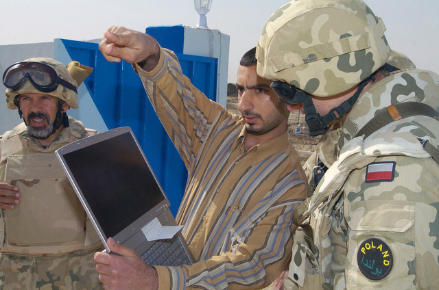 Major (MAJ) Tadeusz Wilkus (right) and Mr. Alex Sadurski (left) from the Polish CIMIC (Civilian Military Corporation) unit, speak with the head contractor of a new police station at the construction site during an assessment of the CIMIC project in AL Diwaniyah, Iraq. The CIMIC conducts various projects aiding the rebuilding of the Iraqi infrastructure during Operation IRAQI FREEDOM