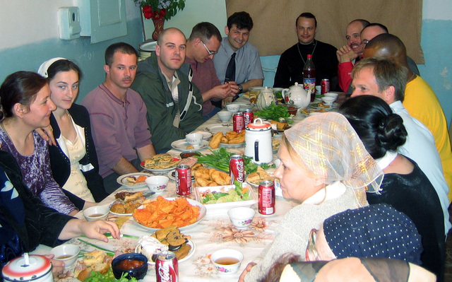 U.S. Air Force Airmen and U.S. Army Soldiers, deployed at Uzbekistan, sit down for a meal with Uzbeks during a humanitarian visit at the Russian Orthodox Church, at Karshi, Uzbekistan,  on April 3, 2005. They group bought food, clothing, shoes, toys and other donat items for the church. (U.S. Air Force PHOTO by STAFF SGT. Brandon Miranda) (Released)
