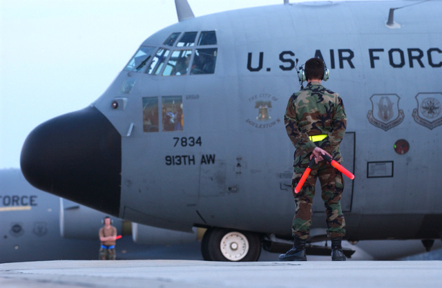 A U.S. Air Force crew chief prepares to marshal a U.S. Air Force Reserve C-130 Hercules cargo aircraft from the 913th Airlift Wing, Willow Grove Air Reserve Station, Pa., during the Joint Force Entry Exercise (JFEX) at Pope Air Force Base, N.C., on April 4, 2005. JFEX is a joint airdrop training designed to enhance service cohesiveness between U.S. Army and Air Force personnel. (U.S. Air Force PHOTO by STAFF SGT. James Harper) (Released)