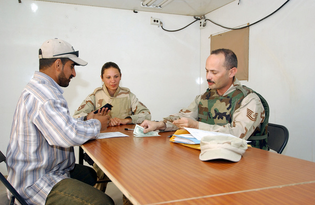 US Air Force (USAF) Technical Sergeant (TSGT) Ray Ashey (right), Non-Commissioned Officer In Charge (NCOIC), Finance Office, 407th Air Expeditionary Group (AEG), Tallil Air Base (AB), Iraq, pays Mr. Usama Hassan Hadi, an Arabic Interpreter with the 407th AEG. USAF STAFF Sergeant (SSGT) Jennifer Pierre-Louis, Contracting Craftsman, 407th AEG Contracting Office, observes the transaction during Operation IRAQI FREEDOM