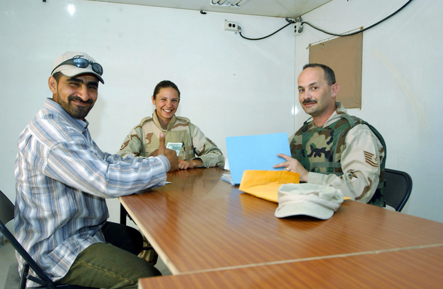 Usama Hassan Hadi (left), an interpreter working for the 407th Air Expeditionary Group, is all smiles after being paid his salary by U.S. Air Force STAFF SGT. Jennifer Pierre-Loius, a 407th AEG contracting craftsman, and TECH. SGT. Ray Ashey, a 407th AEG 407th financial technician, at Tallil AB Iraq, on April 4, 2005. (U.S. Air Force PHOTO by MASTER SGT. Mark Bucher) (Released)
