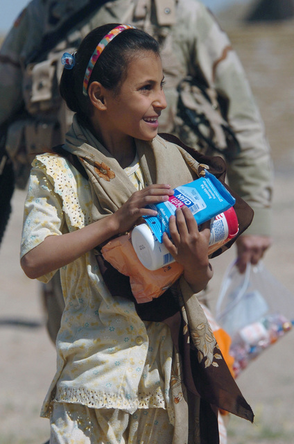 A young girl in a local neighborhood receives treats and personal hygiene products from US Army (USA) Soldiers of the 2nd Battalion (BN)/198th Armor, Quick Response Force (QRF), Mississippi Army National Guard (MSARNG), Amory, Mississippi (MS), part of the 155th Brigade Combat Team (BCT), MSARNG headquartered out of Tupelo, MS. The Soldiers based at Forward Operating Base (FOB) Hotel participating in these activities, are helping establish a stronger relationship with the citizens of Iraq during Operation IRAQI FREEDOM