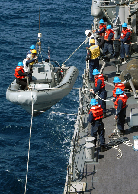 US Navy (USN) Sailors aboard a Rigid Hull Inflatable Boat (RHIB) is raised to the main deck of the USN Arleigh Burke Class Guided Missile Destroyer (Aegis) USS GONZALEZ (DDG 66). (U.S. Navy photo by Photographer's Mate AIRMAN Christopher J. Newsome) (Released)