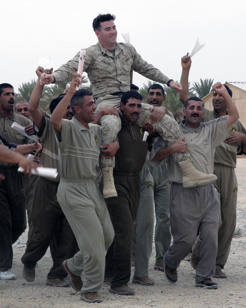 Graduates from the Iraqi Border Patrol Academy hoist US