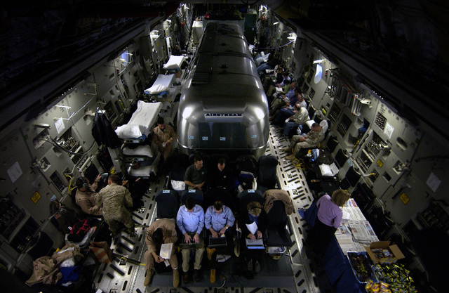"""Members of the Office of the Secretary of Defense (SECDEF) and the traveling press work diligently around the """"Silver Bullet,"""" an Airstream trailer serving as an airborne command center, on board the US Air Force (USAF) C-17A Globemaster III in flight over Iraq"""