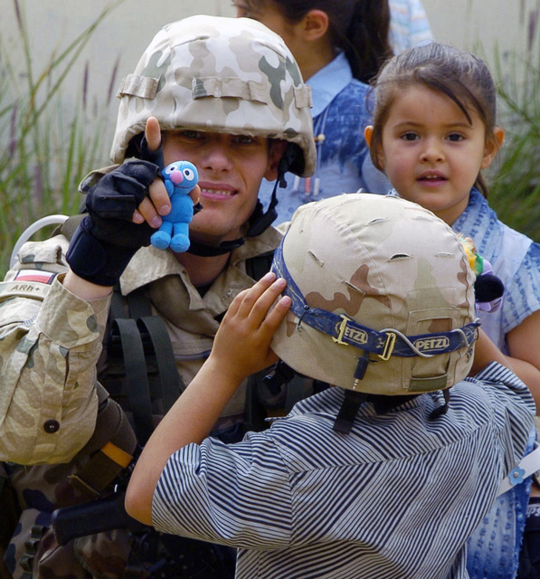 Warrant Office (WO1) Olkowski, Polish Civilian Military Cooperation (CIMIC) unit, distributes toys to children at the Al Azhar Kindergarten School during an humanitarian aid delivery in AL Diwaniyah, Iraq. The CIMIC conducts various projects that aid the rebuilding of the Iraqi infrastructure during Operation IRAQI FREEDOM. (Duplicate image, see also DASD0606833 or search 050414A1566H048)