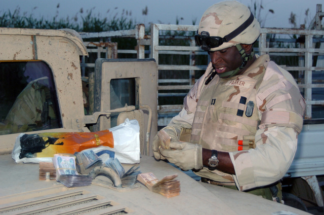 US Army (USA) Captain (CPT) Aaron Parker, Commander, Delta (D) Company (CO), Task Force 2nd Squadron (SQD), 11th Armor Calvary Regiment (ACR), Fort Irwin, California (CA), counts out 8.3 million Iraqi Dinars found on a suspected insurgent during a mounted patrol at Joraf Sakar, Iraq, during Operation IRAQI FREEDOM. The money was confiscated from three Iraqi suspects when they failed to give the right of way to a Delta Company US military convoy patrol. The three Iraqis were arrested and tested positive of gunpowder residue