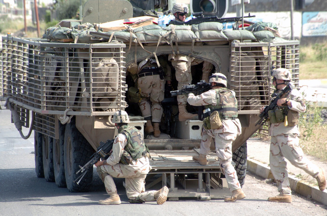 A US Army Soldier (left) from Charley (C) Company (CO), 3rd Battalion (BN), 21st Infantry Regiment (INF REGT), 1ST Brigade (BDE), 25th Infantry Division (ID) Stryker Brigade Combat Team (SBCT), pulls guard while fellow Soldiers load in to the Stryker APC (Armored Personnel Carrier) in Mosul, Iraq, during Operation IRAQI FREEDOM. The guard is armed with a FNMI 7.62 mm M240B machine gun, the others are armed with Special Operation Peculiar Modification (SOPMOD) M4 rifles. The Stryker has a Slat Armor cage, which detonates anti-tank shaped charges away from the vehicle