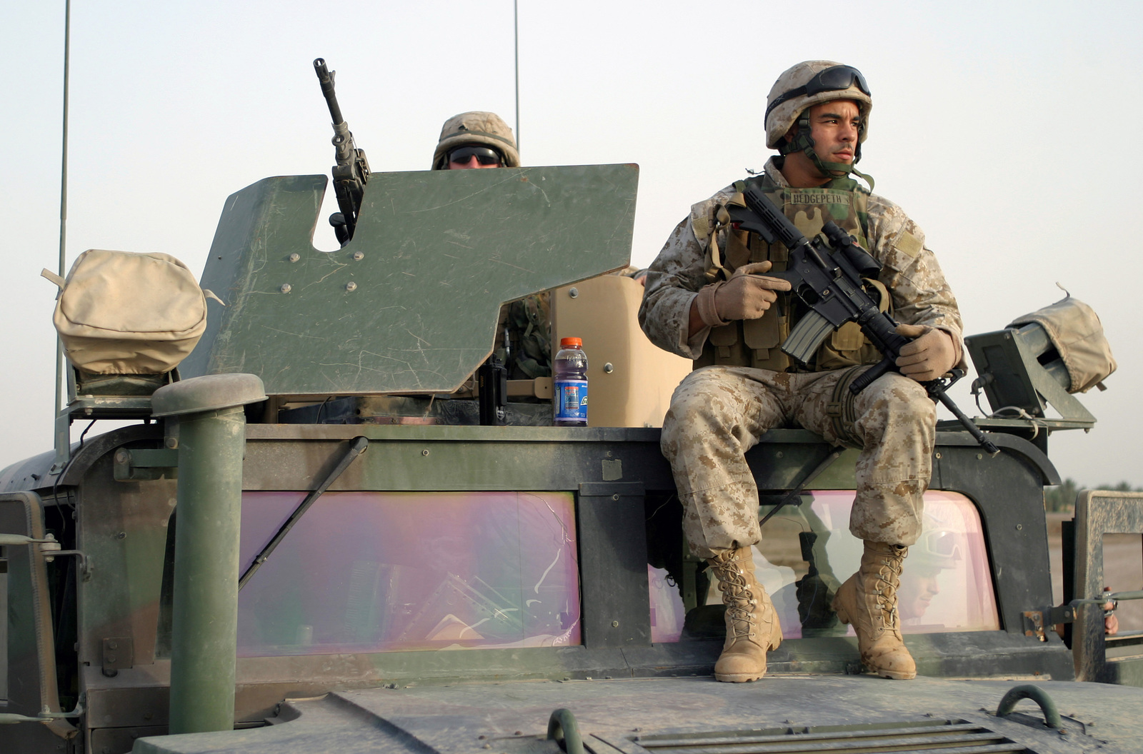 US Marine Corps (USMC) Corporal Sean Adcox (left), mans the 7.62mm M240G machine gun and USMC Sergeant (SGT) Eddie Hedgepeth, carries his 5.56mm M4 Carbine as the sit atop their up armored High-Mobility Multipurpose Wheeled Vehicle (HMMWV). The Marines both are assigned to 2nd Division, Force Service Support Group (FSSG), PSD Platoon, and are providing security along Alternate Supply Route (ASR) Boston, located in Fallujah, Iraq, during Operation IRAQI FREEDOM