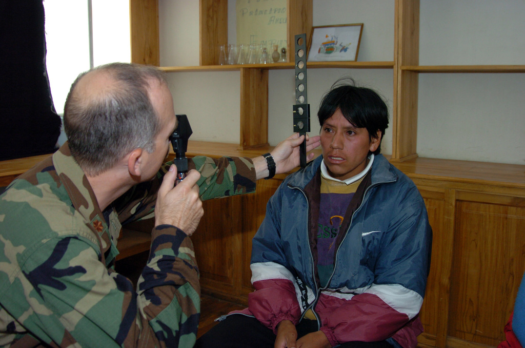 US Air Force MAJ Michael Stevens, an Optometrist with the 82nd Medical Group, Sheppard Air Force Base, Wichita Falls, Texas, left, examines the eyesight of a young man during a Medical Readiness Training Exercise at the Pasto Calle School outside of Quito, Ecuador on 1 June 2005. (US Army PHOTO by Kaye Richey) (Released)