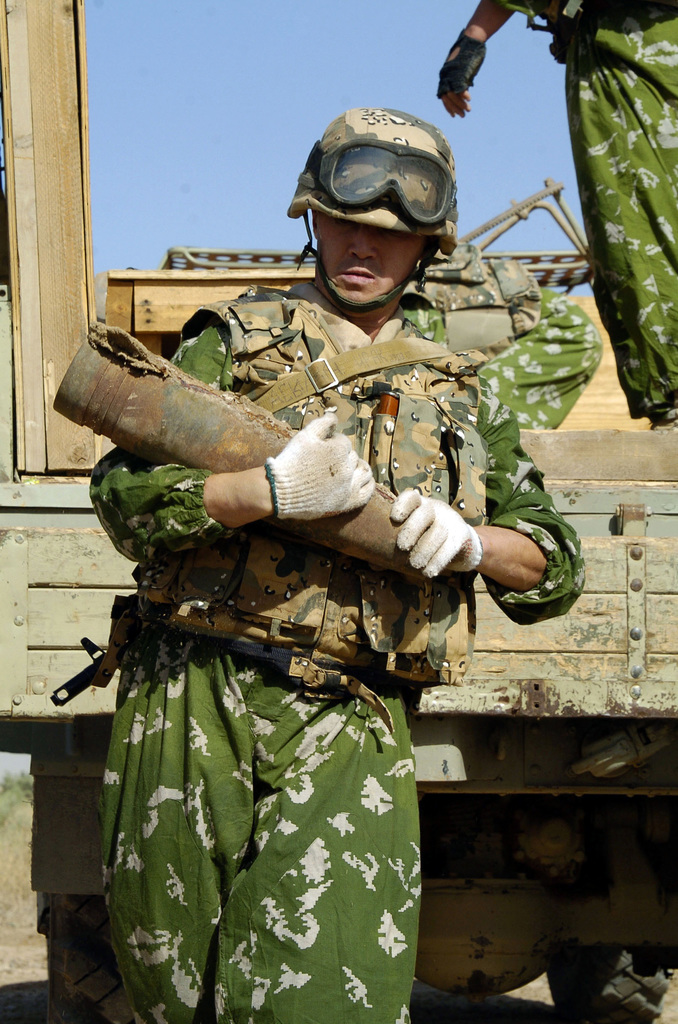 A Kazakhstanian E.O.D. (Explosive Ordance Detachment) Soldier collects old munitions left stock piled from the old Regime, near Camp Delta, Iraq on June 7, 2005.(U.S. Army PHOTO by SGT. Arthur Hamilton) (Released)