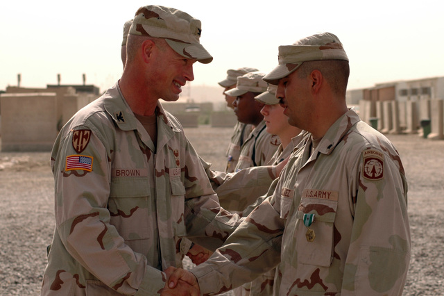 "COL. James B. Brown, commander, 18th Military Police Brigade, Mannheim, Germany, congratulates SPC. Jesse Ordunez, MP, 617th MP Company, Richmond, Ky., at an awards ceremony at Camp Liberty, Iraq, June 16, 2005.  Ordunez was awarded the Army Commendation Medal with""v""device for his actions in a March, 20, 2005, firefight that resulted in the elimination of more than 30 anti-Iraqi forces.. (U.S. Army photo by SPC. Jeremy D. Crisp)"