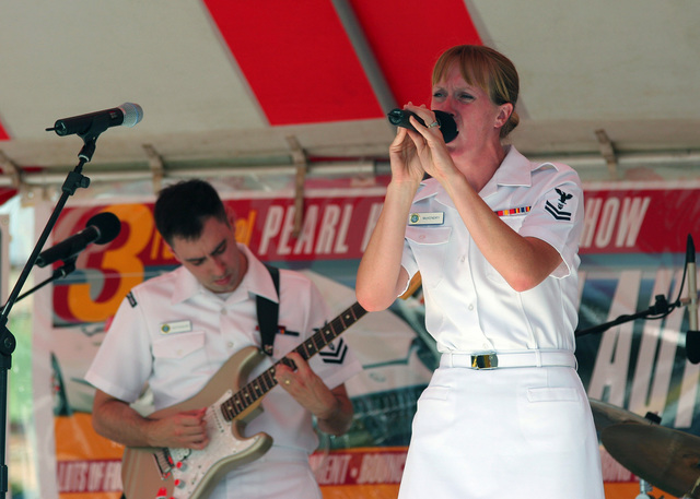 US Navy (USN) Musician Second Class (MU2) Mallory McKendry sings to an audience as USN MU2 Brain Nefferdorf plays the guitar during a public concert at the Pearl Harbor Navy Exchange mall
