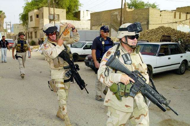 SGT. Anthony Blair and SGT. Ira Turner from the 940th MP Company out of Walton Kentucky, delever 9mm ammunation to an Iraqi Police station during a visit for the purpose of assesing the progress of the Iraqi Police in Dawaniyah on June 21, 2005, Al Dawaniyah, Iraq.(U.S. Army photo by SGT. Arthur Hamilton)(Released)