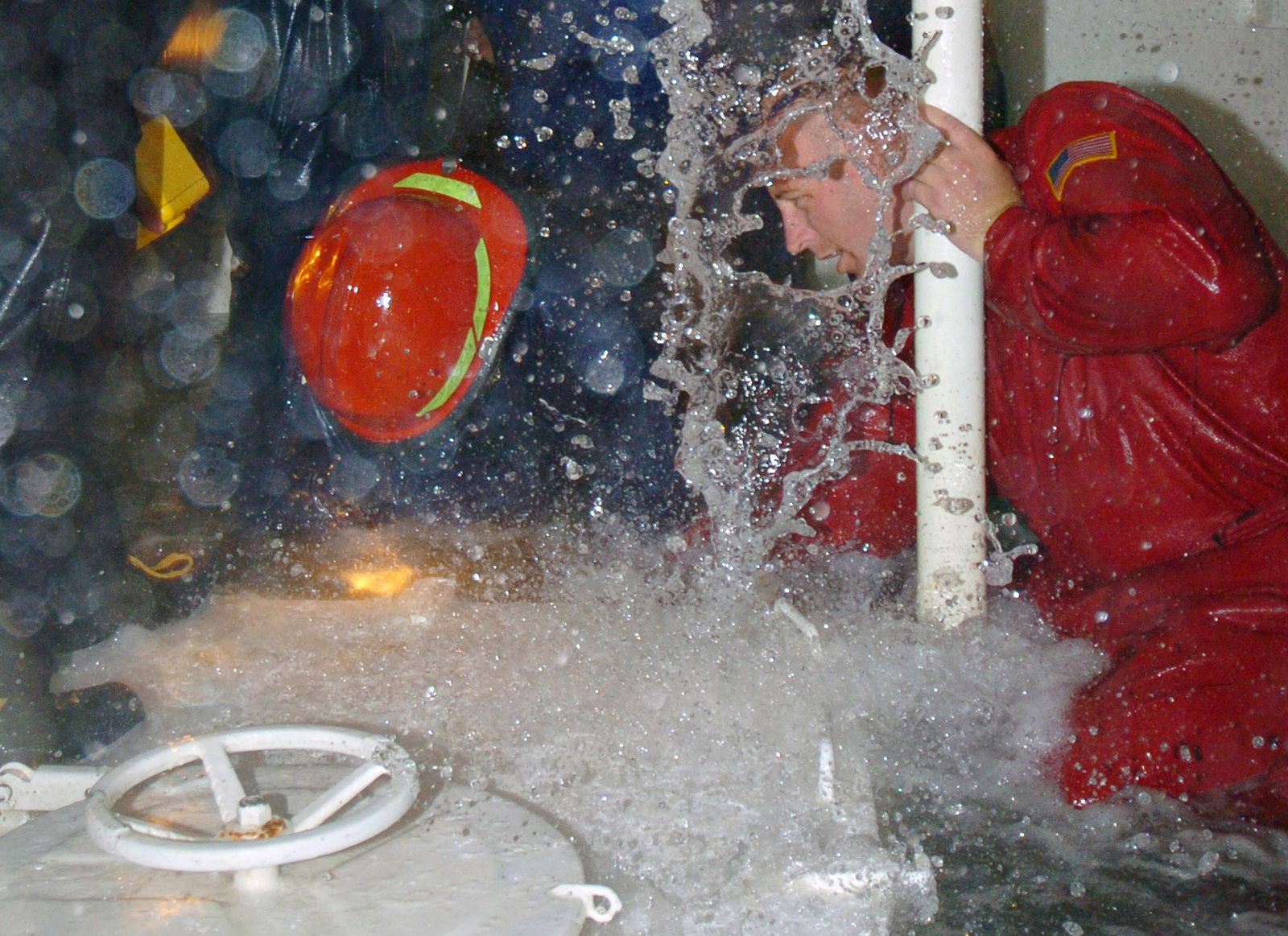 US Navy (USN) Damage Controlman First Class (DC1) Schoen Riley (right), trains Japan Maritime Self Defense Force (JMSDF) Sailors on dewatering techniques during the flooding portion of damage control training. Naval Station San Diego is hosting three JMSDF ships and providing their Sailors with specialized training during their visit