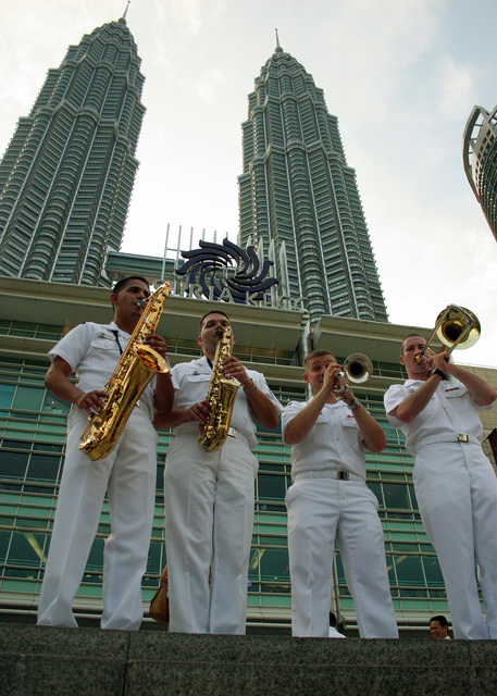 US Navy (USN) members of the Pacific Fleet Band play for an audience near the Petronas Towers in Kuala Lumpur, Malaysia, as part of a 12-day tour in Malaysia. The tour is in celebration of friendship between the United States and Malaysia