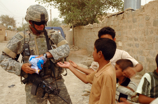 2nd LT. Jason C. Royal, platoon leader, 2nd Platoon, 2nd Battalion, 130th Infantry Regiment, Illinois Army National Guard, hands out candy to Iraqi Children June 23, 2005, in Abu Ghraib, Iraq.  (U.S. Army photo by SPC. Jeremy D. Crisp.)