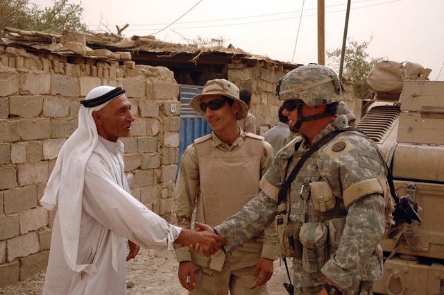 2nd LT. Jason C. Royal, (right), platoon leader, 2nd Plt., 2nd Battalion, 130th Infantry Regiment, Illinois Army National Guard, shakes hand with an Iraqi while interpretor Luis translates June 23, 2005, in Abu Ghraib, Iraq.  (U.S. Army photo by SPC. Jeremy D. Crisp.)