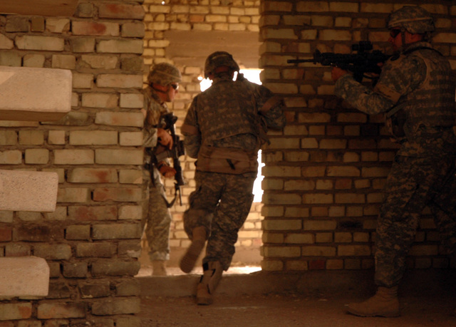 Soldiers from the Illinois Army National Guard's 2nd Platoon, 2nd Battalion, 130th Infantry Regiment, clear a building room by room June 23, 2005 in Abu Ghraib, Iraq.  (U.S. Army photo by SPC. Jeremy D. Crisp.)