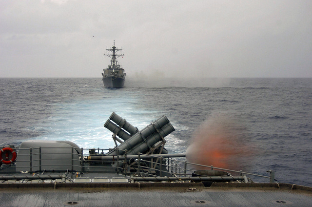 The Ticonderoga Class Guided Missile Cruiser USS COWPENS (CG 63) fires a round from one of her two Mark (MK) 45 5-inch/54 caliber (lightweight) guns during a joint exercise with vessels assigned to the USS KITTY HAWK (CV 63) Carrier Strike Group (CSG). The MK 45 lightweight gun provides surface combatants accurate naval gunfire against fast, highly maneuverable surface targets, air threats and shore batteries during amphibious operations. Behind the gun mount are the ships two quad Harpoon missile launchers. The COWPENS is currently operating in the Coral Sea in support of the combined exercise TALISMAN SABRE 2005. Trailing the COWPENS is the USN Arleigh Burke Class Guided Missile...