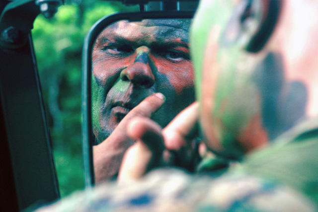 US Marine Corps (USMC) STAFF Sergeant (SSGT) Michael G. Walker, Maintenance CHIEF for Motor Transport Company (MTS), Headquarters Battalion, 3rd Marine Division, applies camouflage face paint, before participating in a Rear Area Operations Field Exercise at the Central Training Area (CTA), located in Okinawa, Japan