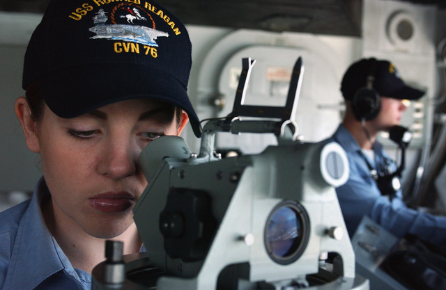 US Navy (USN) Aviation Ordnanceman Third Class (AO3) Dylan Dentremont (right) stands gun control watch under instruction, while USN GUNNER's Mate First Class (GM1) Valerie McNairy uses a gyro compass to check the bearing on a point of reference from the Nimitz Class USS RONALD REAGAN (CVN 76). The REAGAN is returning to its homeport at Naval Air Station North Island (NASNI) after conducting routine carrier operations