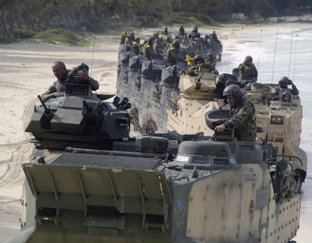 A convoy of US Marine Corps (USMC) AAV7A1 Amphibious Assault Vehicles, assigned to the 3rd Amphibious Assault Battalion, moves along the shore of the Pacific Missile Range Facility located at Oahu, Hawaii (HI), after completing combat amphibious training exercises