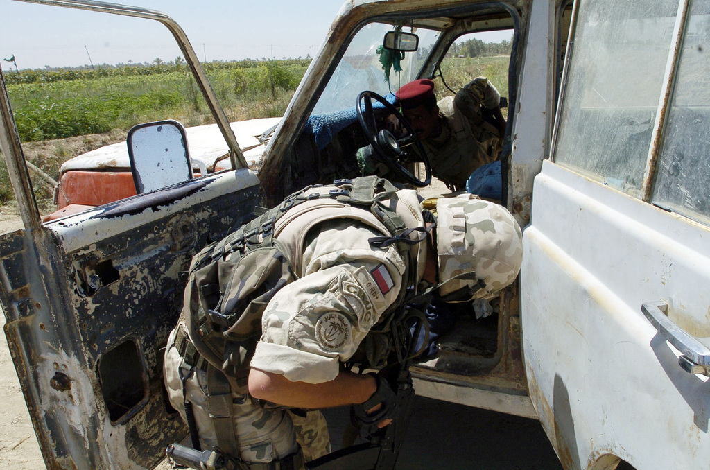 """An Iraqi Soldier searches a vehicle in northern Babil Provence with the assistance of Soldiers from the Polish 2nd Battle Group, during Operation""""Hausar Wings""""on June 28, 2005 in Babil Provence, Iraq.(U.S. Army photo by SGT. Arthur Hamilton)(Released)"""
