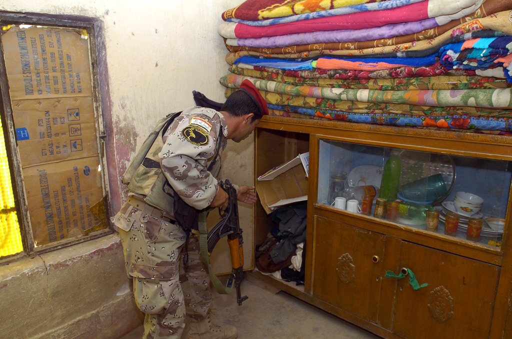 """Iraqi Soldiers search farm houses in northern Babil Provence with the assistance of Soldiers from the Polish 2nd Battle Group, during Operation""""Hausar Wings""""on June 28, 2005 in Babil Provence, Iraq.(U.S. Army photo by SGT. Arthur Hamilton) (Released)"""