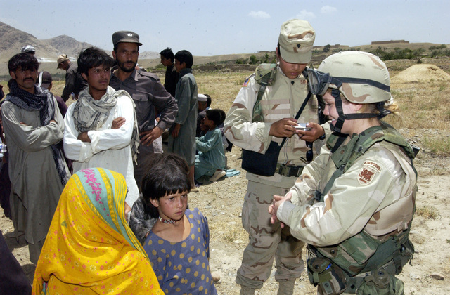SPC. Christine Prescott, 690th Military Police Company, passes out pens and pencils to local children during a Humanitarian Assistance mission for Syed river flood victims outside Bagram, Afghanistan on June 30, 2005. The Soldiers distributed food, water, clothing, and hygiene products to the flood victims. (U.S. Army photo by SGT. Christopher Kaufmann) (Released)