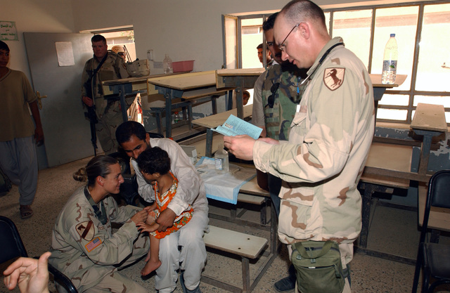 (050702-A-9144B-104)On July 2, 2005 Major Shawn Doyle, Regimental Surgeon for 1ST Squadron 11th Armored Cavalry Regiment, reads the medical record of a small child with the aid of an interpreter as Sergeant Theresa Szczerban, a medic from Headquarters and Headquarters Company, 612th Engineer Battalion talks to the child. MAJ Doyle and SGT Szczebran are working at a free medical clinic set up in Abu Gharaib neighborhood, Baghdad, Iraq. 1/11 ACR and the 612 Engineer Battalion are deployed in support of Operation Iraqi Freedom.(050702-A-9144B-104) (US ARMY PHOTO by: SPC Timothy J. Belt 55th Signal Company (Combat Camera) (RELEASED)