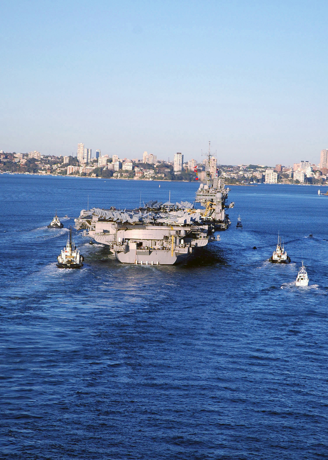 Stern on view of the US Navy (USN) Aircraft Carrier, USS KITTY HAWK (CV 63), being escorted by commercial tug boats and harbor patrol craft, as it transits the harbor at Sydney, Australia. The KITTY HAWK has just completed operations as part of Exercise TALISMAN SABRE 2005