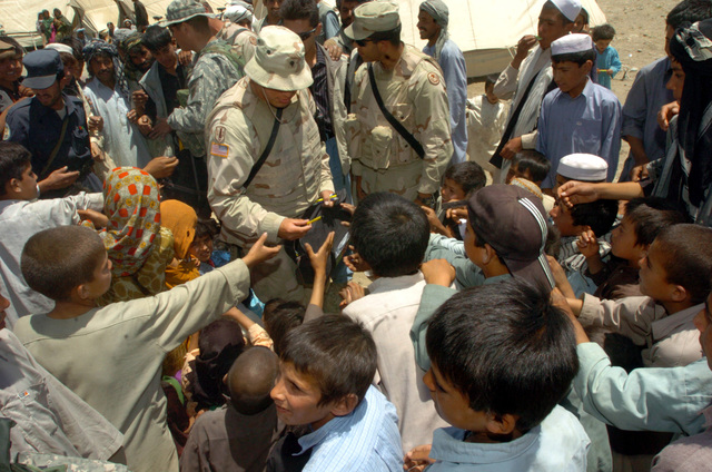 A soldier from Task Force Eagle hands a pen to a local child during a Humanitarian Assistance mission for flood victims outside Bagram, Afghanistan on July 4, 2005.  (Released)  (U.S. Army photo by SPC Harold Fields)