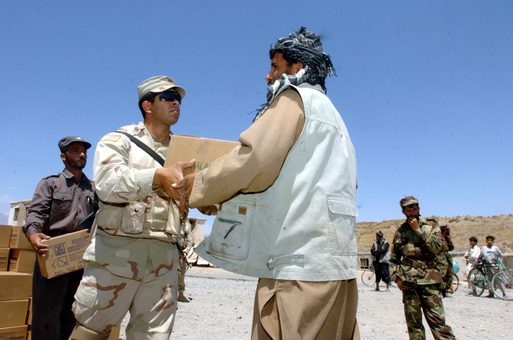 A soldier from Task Force Eagle hands out food and water during a Humanitarian Assistance mission for flood victims outside Bagram, Afghanistan on July 4, 2005.  (Released)  (U.S. Army photo by SPC Harold Fields)
