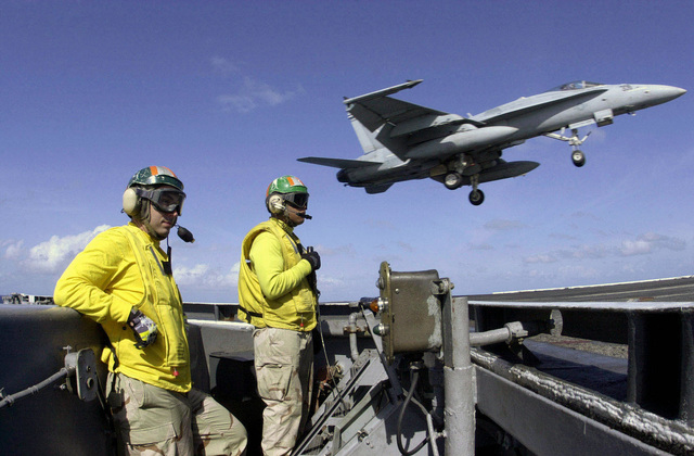 US Navy (USN) Lieutenants (LT) Tony Meyers and Derecy Brown stand watch as a USN F/A-18E Super Hornet fighter, Strike Fighter Squadron 14 (VFA-14), Tophatters, Naval Air Station (NAS) Lemoore, California (CA), conducts a wave-off over the flight deck of the USN Aircraft Carrier USS NIMITZ (CVN 68). The Nimitz Strike Group is currently on a regularly scheduled deployment in support of the Global War on Terrorism (GWOT)