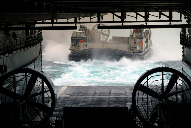 A US Navy (USN) Landing Craft, Air Cushion (LCAC), Assault Craft Unit Five (ACU-5), Marine Corps Base (MCB) Camp Pendleton, California (CA), makes its approach into the well deck aboard the Amphibious Dock Landing Ship USS HARPERS FERRY (LSD 49) on the East China Sea. The HARPERS FERRY is currently participating in Amphibious Specialty Training (AST), certifying the well deck for operations
