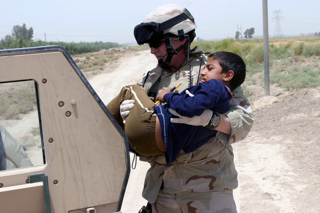 US Army (USA) SPECIALIST (SPC) Morrie Douglass, a Medical Technician with the 98th Cavalry, 4th Platoon, carries a young boy to an M998 High-Mobility Multipurpose Wheeled Vehicle (HMMWV) where he can care for the boys rusty nail injury near his home in Hasawa, Iraq (IRQ), during Operation IRAQI FREEDOM