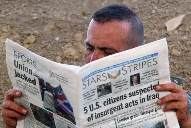 US Army (USA) SPECIALIST (SPC) Rodney Davidson from Bravo Company, 2 Battalion-121st Infantry Regiment reads a Stars and Stripes newspaper near Al-Radwnea, Iraq (IRQ), during Operation IRAQI FREEDOM