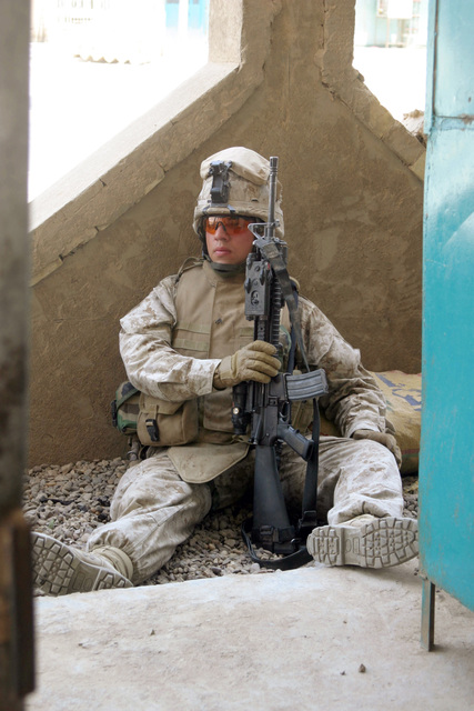 US Marine Corps (USMC) Lance Corporal (LCPL) Brian Rodriguez, 1ST Battalion (BN), 6th Marine Regiment (MAR REGT), Bravo Company (B CO), pauses for a brief second to rest during a knock and cordon conducted within the inner city of Fallujah, Iraq (IRQ). He is armed with a 5.56 mm M16A2 rifle. The 2nd Marine Division (MAR DIV) and MNF-W (Multi-National Force-West) conducts counter-insurgency operations with Iraqi Security Forces (ISF) to isolate and neutralize Anti-Iraqi Forces during Operation IRAQI FREEDOM
