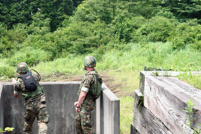 US Marine Corps (USMC) Lance Corporal (LCPL) Gregory E. Blackburn (left), Infantry Rifleman, Echo (E) Company (CO), 2nd Battalion (BN), 25 Marines (MAR), throws an M67 fragmentation grenade at the Grenade Range Camp Fuji, Japan during exercise Fuji Incremental Training Program (FITP) 2004
