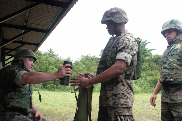 US Marine Corps (USMC) Lance Corporal (LCPL) Sinclair (left), Infantry Rifleman, Echo (E) Company (CO), 2nd Battalion (BN), 25 Marines (MAR), hands out two M67 fragmentation grenades each to Marines who completed practice training at the Grenade Range Camp Fuji, Japan during exercise Fuji Incremental Training Program (FITP) 2004