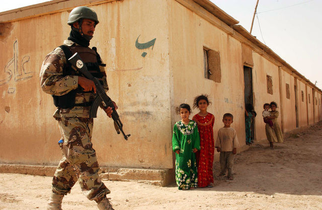 Children watch as 3rd Battalion ,1ST Brigade 5th division soldiers patrol Al Showka village during a presence Patrol, Diyala province, Iraq, July 12, 2005.(U.S. Army photo by SPC. Gul A. Alisan) (Released)