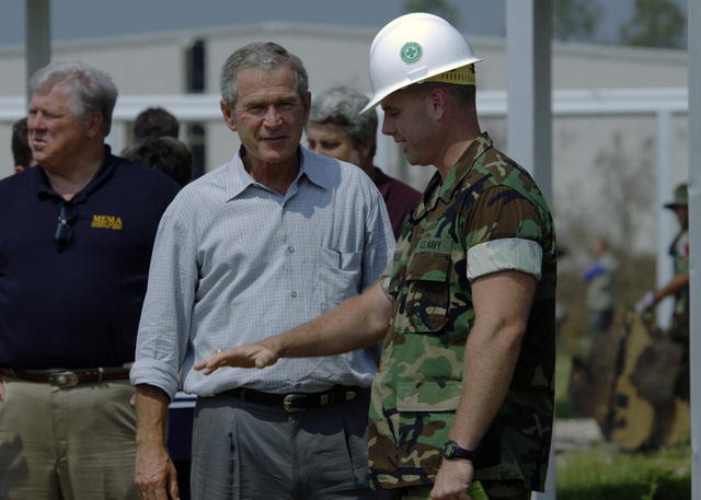 US President George W. Bush listens as US Navy (USN) Lieutenant Junior Grade (LTJG) Sam Werschky, assigned to Naval Mobile Construction Battalion One (NMCB-1), describes the clean-up efforts underway at the 28th Street Elementary School in Gulfport, Mississippi (MS). President Bush is currently visiting the Gulf Coast region to assess the damage and disaster recovery efforts from Hurricane Katrina. The USN is currently involved in Hurricane Katrina humanitarian assistance operations, led by the Federal Emergency Management Agency (FEMA), in conjunction with the Department of Defense (DOD)