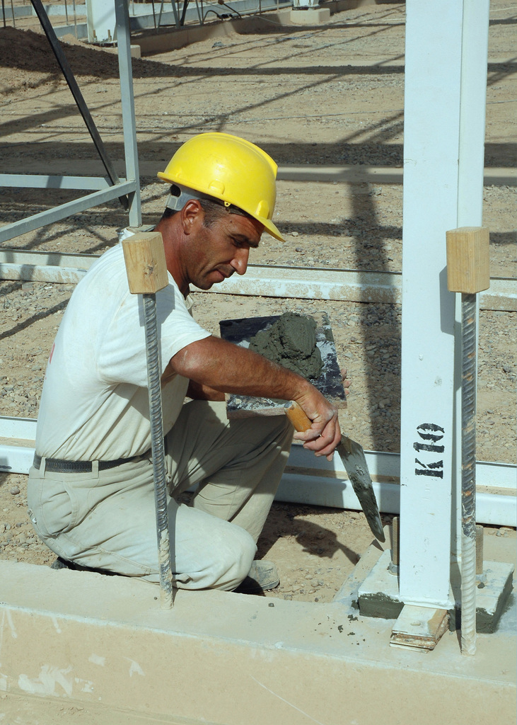 An Iraqi civilian construction worker cements a steel support column, to be used as the main structural element, as he helps build the new medical supply warehouse at the Logistical Support Area (LSA) Balad, Balad Air Base (AB), Salah Ad Din Province, Iraq (IRQ), during Operation IRAQI FREEDOM
