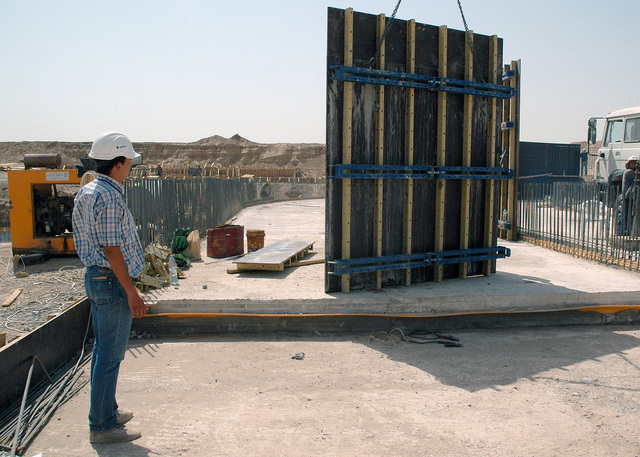 Iraqi civilian construction workers use a truck mounted heavy lift arm to place a pre-fabricated support wall into position as they build a wastewater treatment facility at Logistical Support Area (LSA) Anaconda, Balad Air Base (AB), Salah Ad Din Province, Iraq (IRQ), during Operation IRAQI FREEDOM