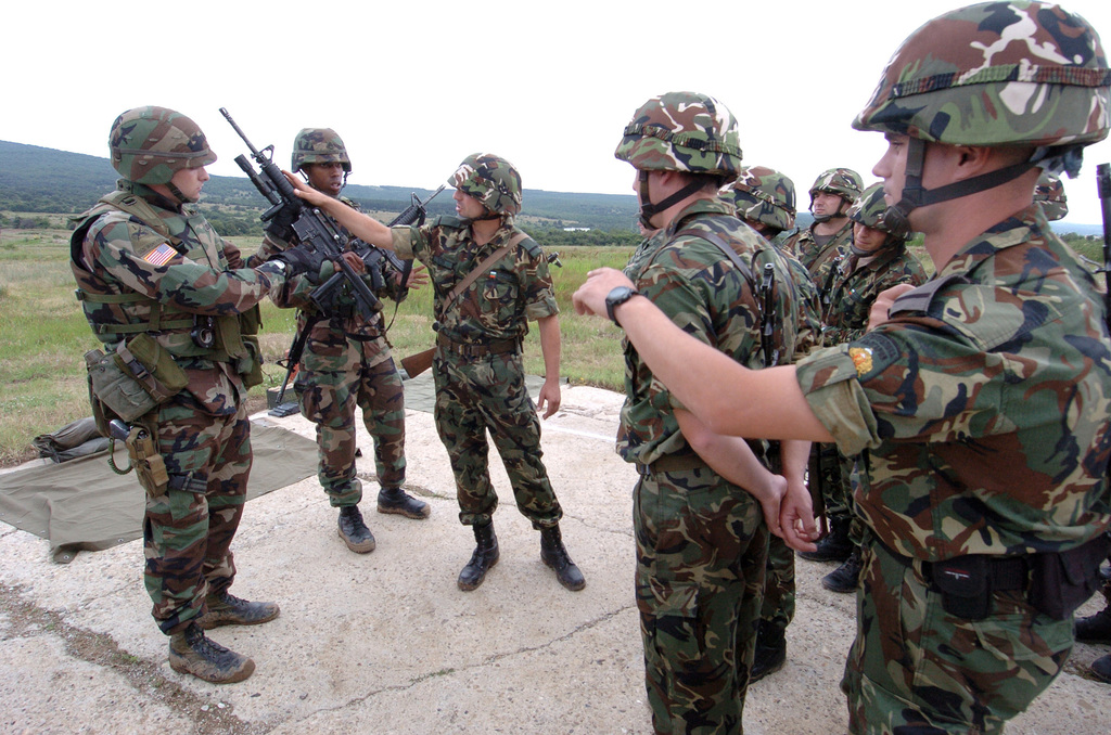 U.S. Army SGT. Joshua Dumond, Bandit Troop, 1ST Squadron, 1ST Cavalry, demonstrates with the help of Bulgarian CPL. Alexander Kulev to Bulgarian Soldiers the proper use of the M4 Carbine during joint small arms training at Novo Selo Training Area, Bulgaria. (U.S. Army PHOTO by SGT. Kevin S. Abel) (Released)