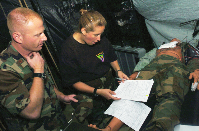 Delaware Air National Guard (DEANG) Captain (CPT) Rachel Stevens, a nurse assigned to the 166th Medical Group (MG), goes over her medical notes with a colleague after a medical exercise scenario in support of Patriot Exercise 2005.  Patriot Exercise 2005, is the largest annual exercise held across the United States. (SUBSTANDARD)