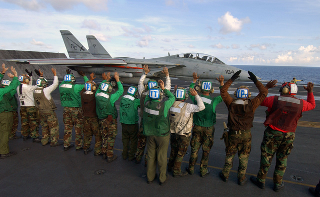 """US Navy (USN) Flight Deck Crewmembers aboard the Nimitz Class: Aircraft Carrier, USS THEODORE ROOSEVELT (CVN 71), give an impromptu send-off to an F-14D Tomcat aircraft from Fighter Squadron Three Two the """"Swordsmen marking the final time the F-14 will take part in flight operations while embarked aboard Truman. VF-32 will shortly begin the process of transitioning to the newer F/A-18F Super Hornet aircraft"""
