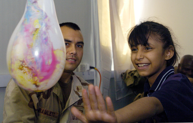 CAPT. Dewayne Branlett from the 538 CSC (Combat Stress Relief) uses hand-eye coordination exercises as a form of physical rehabilitation therapy to an Iraqi child suffering from cerebral palsy, on July 20, 2005 in Camp Echo, Iraq.(U.S. Army photo by SGT. Arthur Hamilton)(Released)